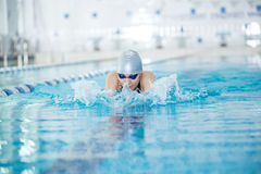 Young girl in goggles swimming breaststroke stroke Stock Image