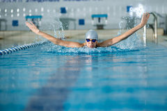 Young girl in goggles swimming butterfly stroke style. Young woman in goggles and cap swimming butterfly stroke style in the blue water indoor race pool Stock Photo