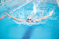 Young girl in goggles swimming butterfly stroke style. Young woman in goggles and cap swimming butterfly stroke style in the blue water indoor race pool Stock Photos