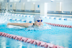 Young girl in goggles swimming butterfly stroke style. Young woman in goggles and cap swimming butterfly stroke style in the blue water indoor race pool Stock Images