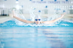Young girl in goggles swimming butterfly stroke style Stock Photos