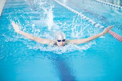 Young girl in goggles swimming butterfly stroke style Stock Photography