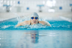 Young girl in goggles swimming butterfly stroke. Young woman in goggles and cap swimming butterfly stroke style in the blue water indoor race pool Stock Photos
