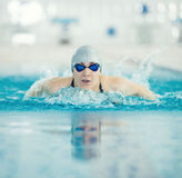 Young girl in goggles swimming butterfly stroke. Young woman in goggles and cap swimming butterfly stroke style in the blue water indoor race pool Royalty Free Stock Images