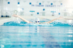 Young girl in goggles swimming butterfly stroke. Young woman in goggles and cap swimming butterfly stroke style in the blue water indoor race pool Stock Image