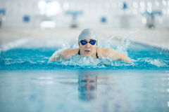 Young girl in goggles swimming butterfly stroke. Young woman in goggles and cap swimming butterfly stroke style in the blue water indoor race pool Stock Images