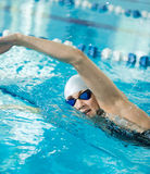 Young girl in goggles swimming front crawl stroke style Stock Images