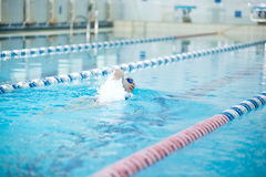 Young girl in goggles swimming front crawl stroke Royalty Free Stock Images