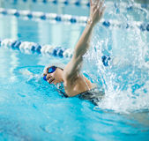Young girl in goggles swimming front crawl stroke. Young woman in goggles and cap swimming front crawl stroke style in the blue water indoor race pool Royalty Free Stock Photography