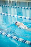 Young girl in goggles swimming front crawl stroke Stock Photos