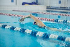 Young girl in goggles swimming front crawl stroke Royalty Free Stock Image