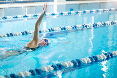 Young girl in goggles swimming front crawl stroke Royalty Free Stock Photos