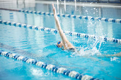 Young girl in goggles swimming front crawl stroke Stock Images