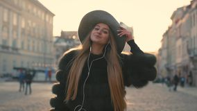 Young girl Going the city and listening to music on the phone. Attractive young girl Going the city and listening to music on the phone and smiling happily stock video footage