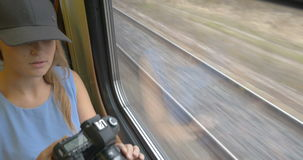 Young girl going by train and taking pictures. Pretty blonde woman in cap using professional camera to make photos through the train window. View to the railway stock video footage