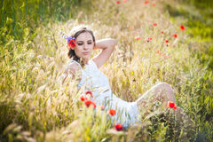 Young girl on golden wheat field Stock Photos