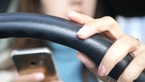 A young girl in a good mood at the wheel of a car, clings to the wheel, knocks on it with her fingers, dances, the Stock Image