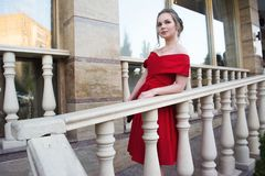 A young girl with a gorgeous hair and makeup, in a red evening dress celebrating graduation and enter to University. stock photo