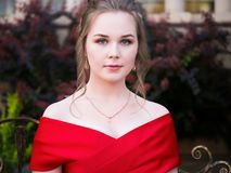 A young girl with a gorgeous hair and makeup, in a red evening dress celebrating graduation and enter to University. royalty free stock photos