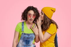 Young girl gossiping with friend. Young female in bright casual outfit whispering secret to ear of astonished friend while standing against pink background royalty free stock photos