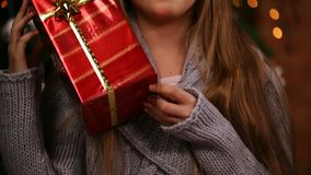 Young girl grabbing a christmas present lifting it to her face, laughing. Young girl hands grabbing a christmas present lifting it to her face, laughing with joy stock video footage