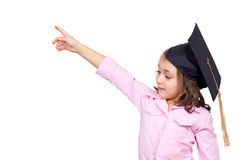 Young girl in graduation cap and gown pointing Stock Photo