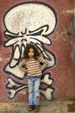 Young girl grafitti wall. Young girl in front of a grafitti wall with painted skul stock photos