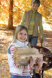Young girl and grandmother doing yard work in autumn Stock Images