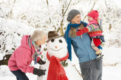 Young Girl With Grandmother And Mother. Building Snowman In Garden Stock Photos