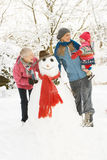 Young Girl With Grandmother And Mother. Building Snowman In Garden Royalty Free Stock Photo