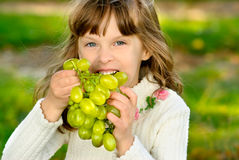 Young girl with grapes Stock Photos
