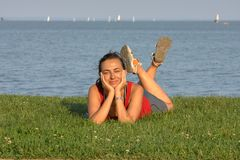 Young girl on the grass on the beach in summertime stock images