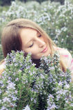 Beautiful young girl in a grass field of rosemary Royalty Free Stock Images