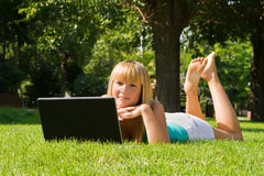 Young girl on the grass with laptop. Young girl on the grass with notebook Royalty Free Stock Image