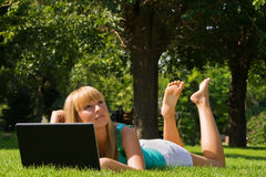 Young girl on the grass with notebook Stock Image