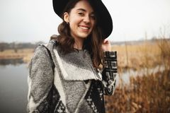 Young girl in gray cardigan and black hat smiles and poses on the shore of a lake stock photo
