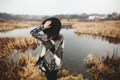 Young girl in gray cardigan poses on the shore of a lake. Back view royalty free stock photography