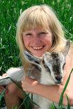 The young girl with gray  goat Stock Image