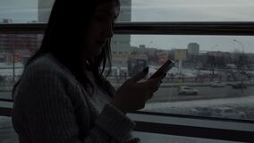 Young girl in a gray sweater with a phone in a cafe by the window on the megalopolis background. Young girl in a gray sweater with a phone in a cafe by the stock video