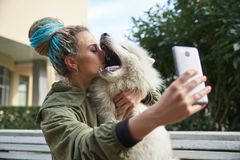 young girl in green coat and multicolored dreadlocks makes a selfie on your smartphone posing with white Samoyed dog in royalty free stock image