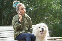 Young girl in green coat and multicolored dreadlocks talking on royalty free stock image