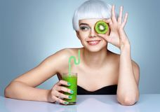 Young girl with green detox smoothie and a half of kiwi in front of her face on blue background Royalty Free Stock Image