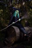 Young girl with green hair and broom in suit of witch in forest. Halloween time Royalty Free Stock Photo