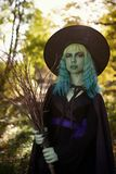 Young girl with green hair and broom in suit of witch in forest. Halloween time.  royalty free stock images