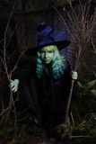 Young girl with green hair and broom in suit of witch in forest. Halloween time Royalty Free Stock Photos