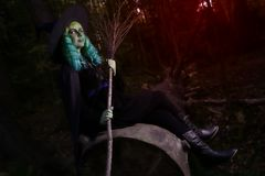 Young girl with green hair and broom in suit of witch in forest. Halloween time Royalty Free Stock Images