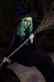 Young girl with green hair and broom in suit of witch in forest. Halloween time.  stock photo