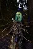 Young girl with green hair and broom in suit of witch in forest. Halloween time.  stock photography