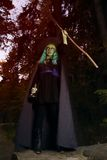 Young girl with green hair and broom in suit of witch in forest. Halloween time Royalty Free Stock Photography