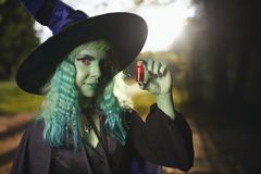 Young girl with green hair and skin suit of witch in forest holds small bottle with red potion. Halloween time Stock Image